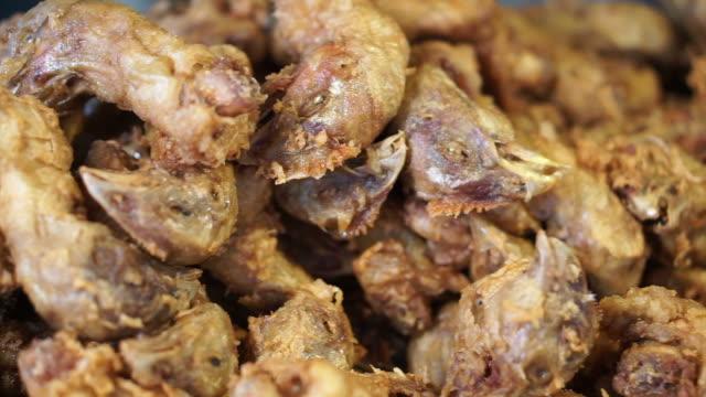 spaventoso mercato umido asiatico cibo fritto testa di pollo. per lo più fatto per il cibo per cani - mammifero video stock e b–roll