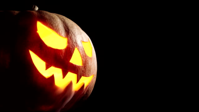 vídeos de stock e filmes b-roll de scary carved halloween pumpkin in hot burning hell fire flames. the big helloween pumpkin has a mad face with glowing eyes and also a smoke in its mouth and teeth - halloween