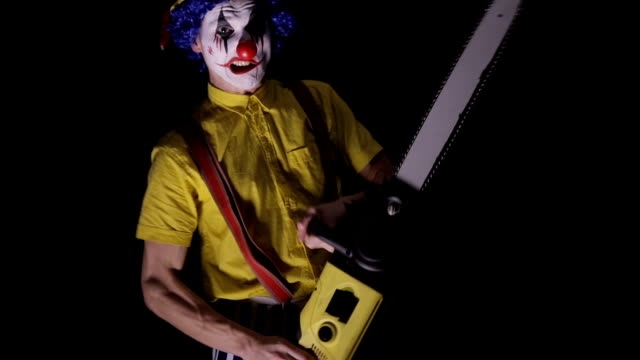 scary clown with a chainsaw in the dark. clown murderer threatening you - motosega video stock e b–roll