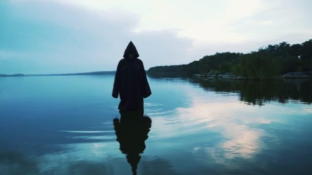 vídeos de stock e filmes b-roll de scary figure in black mantle in the river. - capuz