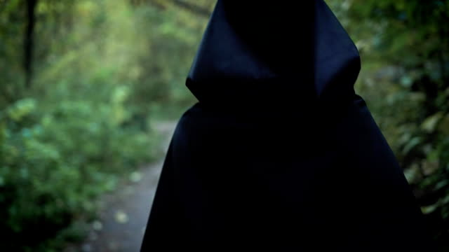 Scary girl is walking in forest Grim woman walks around the forest in the dark cloak. She goes deep into the woods. vampire stock videos & royalty-free footage