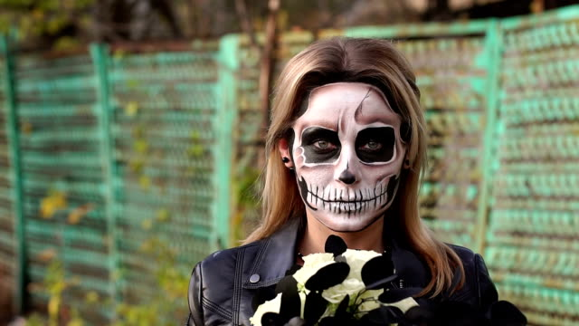 scary girl with make-up on a halloween with a bouquet of black flowers. - театральный грим стоковые видео и кадры b-roll