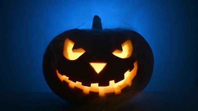 Scary glowing face of Halloween pumpkin in blue smoke.