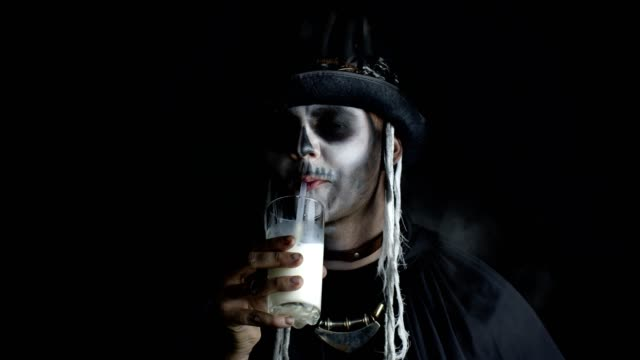 Scary guy in carnival costume of Halloween skeleton looking at camera, drinks milk from a glass