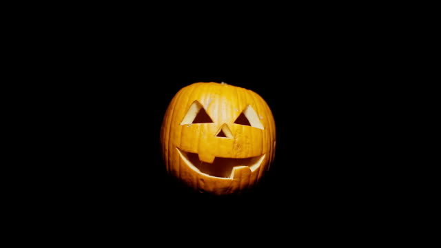 Scary Jack o'lantern appears out of the darkness. Isolated Light-orange pumpkin for Halloween or All Saints Day on a black background. The light moves to the right video