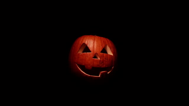 Scary Jack o'lantern appears out of the darkness. Isolated pumpkin for Halloween or All Saints Day on a black background video
