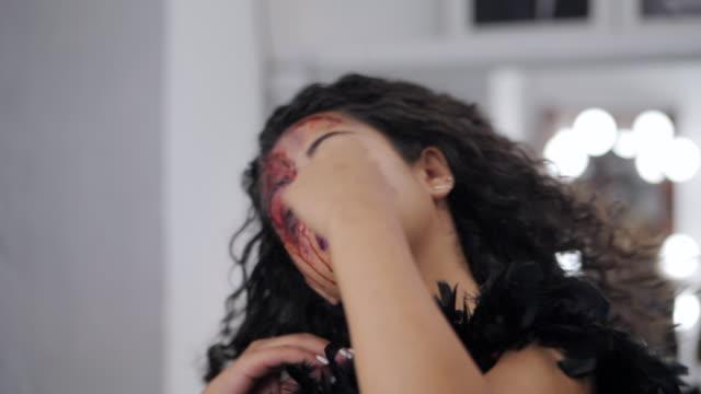 skrämmande porträtt av ung flicka med halloween blod makeup. vacker latin kvinna sätter det lockiga håret ner nära spegeln i omklädningsrummet. slow motion - makeup artist bildbanksvideor och videomaterial från bakom kulisserna