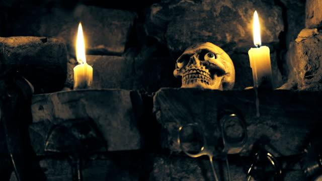 stockvideo's en b-roll-footage met eng schedel in plaats voor rituelen met instrumenten en kaarsen - swearing
