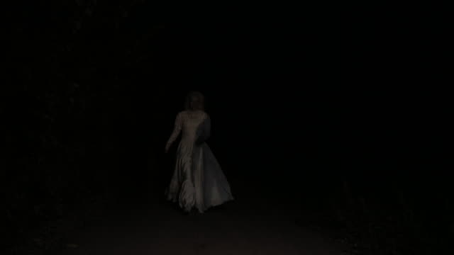 Scary witch appearing from the dark