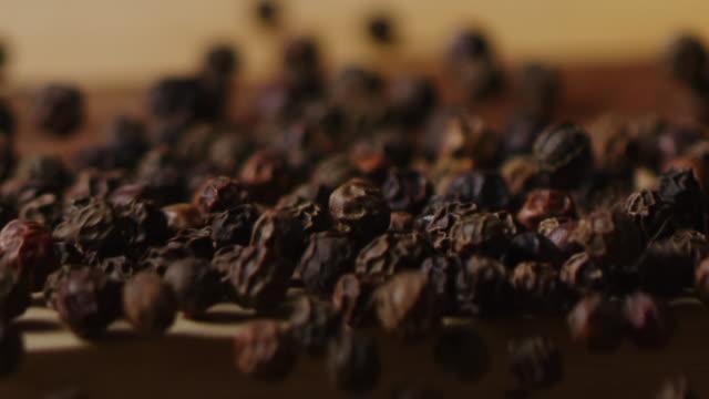 Scattering black pea pepper on kitchen table macro shot