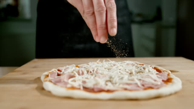SLO MO Scattering spices over the pizza