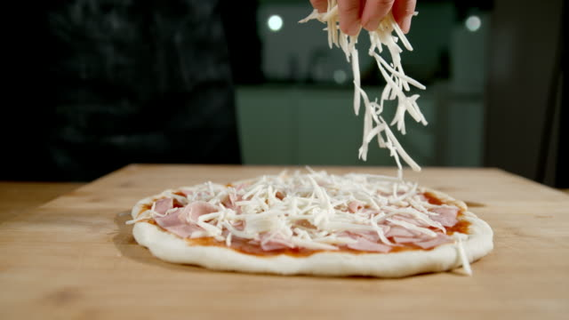 slo mo scattering the cheese over the pizza - pizza filmów i materiałów b-roll
