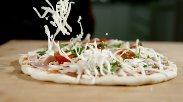vídeos de stock e filmes b-roll de slo mo scattering the cheese over the pizza - pizza
