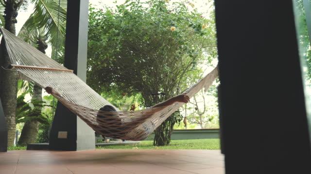 現場的吊床鏡頭,綁在房子前面,亞洲婦女坐在和擺動吊床,在家裡放鬆。 - 鬆弛 個影片檔及 b 捲影像