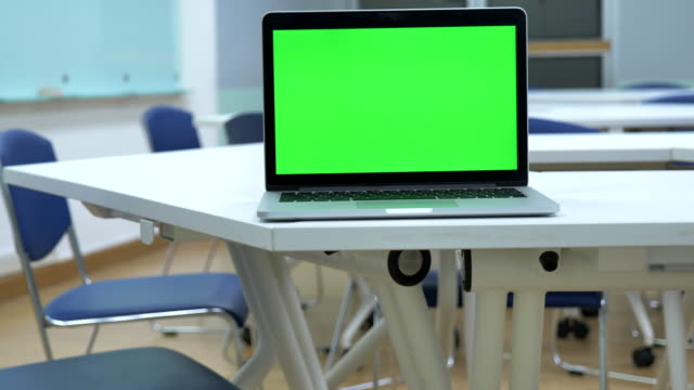 Scene dolly shot of laptop computer showing green chroma key screen stands in the classroom. Technology In the Background , Concept of technology background, Back to school