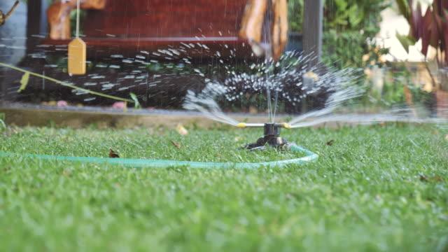 scen dolly skott av sprinkler på gräset hemma, begreppet dag i livet objekt - gräsmatta odlad mark bildbanksvideor och videomaterial från bakom kulisserna