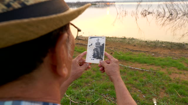 Scene of asian senior military veteran is sitting and looking at his old pictures when he was in army ,