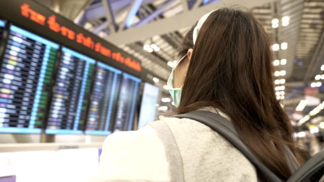 亞洲婦女戴口罩保護冠狀病毒的場景,站在飛行板上檢查航班 - travel 個影片檔及 b 捲影像