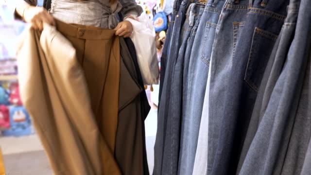 scen av asiatiska unga kvinna shopping för jeans i klädaffär, begreppet semester slutet av veckan, livsstil asiatiskkvinna - byxor bildbanksvideor och videomaterial från bakom kulisserna