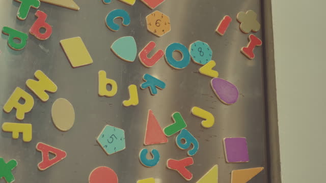 Scene of detail of colorful magnets on a fridge door. Make by father's and mother's with son playing at home, Concept of family objects Video Scene of detail of colorful magnets on a fridge door. Make by father's and mother's with son playing at home, Concept of family objects (4K) magnet stock videos & royalty-free footage