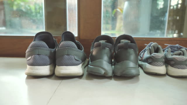 scene of father's shoes and mother's shoes next to son shoes near front the door at home, concept of family objects - обувь стоковые видео и кадры b-roll