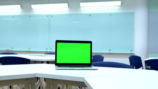 Scene of laptop computer showing green chroma key screen stands in the classroom. Technology In the Background , Concept of technology background