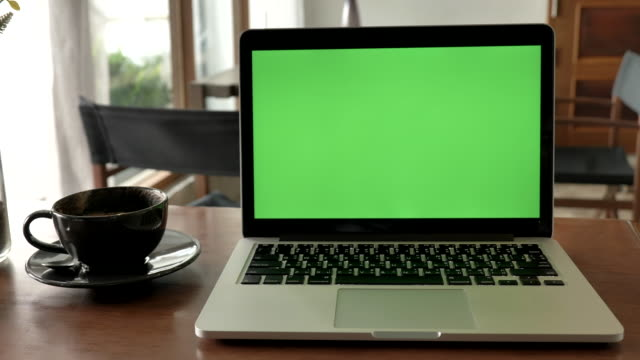 Scene of  laptop computer showing green chroma key screen stands on a desk in the coffee shop. Technology In the Background , Concept of technology background
