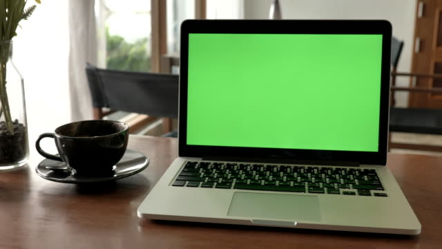 Scene of laptop computer showing green chroma key screen stands on a desk at home. Technology In the Background , Concept of technology background and Day in the Life Objects