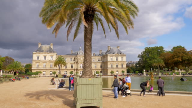 Scene of Luxembourg Gardens with Palace and Pool. Sightseeing of Paris, France PARIS, FRANCE - SEPTEMBER 29, 2017: Scene with medieval Palace, Pool with fountain and people relaxing in Luxembourg Gardens. Sightseeing of city palace stock videos & royalty-free footage