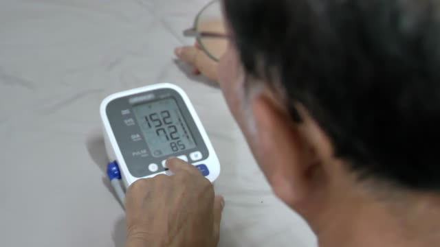 Scene of senior asian male measures his pressure at home Video scene of senior asian male measures his pressure at home (4K) blood pressure gauge stock videos & royalty-free footage
