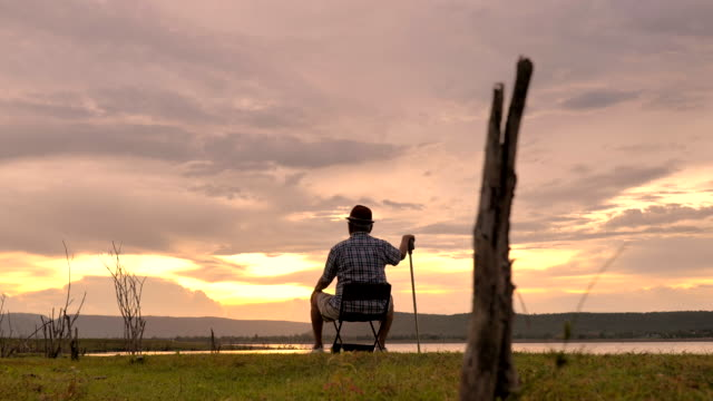 Scene of senior asian male sit down with holding walking cane enjoying viewing nature near the lake, He are happy and have fun on holidays, Relaxation moment. Concept of senior natural everyday life outdoors