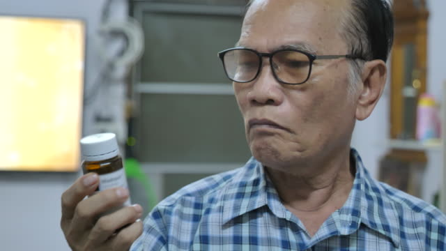 Scene of senior asian man putting on glasses to read her prescription bottle