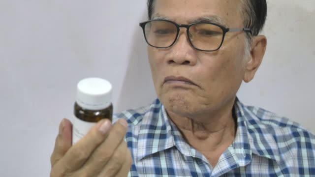 Scene of senior asian man putting on glasses to read her prescription bottle at home Video scene of senior asian man putting on glasses to read her prescription bottle at home (4K) pill bottle stock videos & royalty-free footage