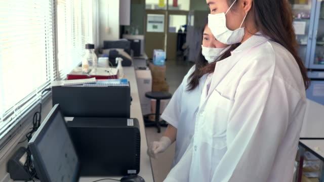 stockvideo's en b-roll-footage met scène van twee wetenschappers met behulp van computer in onderzoek op laboratorium, concept wetenschap en technologie in het laboratorium, wetenschappers die werkzaam zijn in het laboratorium - mid volwassen vrouw