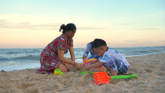 Scene slow motion of asian family making sand castle on beach in summer, Asian family is playing on the beach and making sand castle in summer holiday, Concept holiday and travel in summer