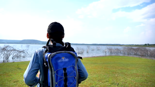 scene slow motion of asian woman backpacker is walking and enjoying view nature near the lake in the summer holidays. she is happy and have fun on holidays, relaxation moment. concept of teen natural everyday life outdoors - турист с рюкзаком стоковые видео и кадры b-roll
