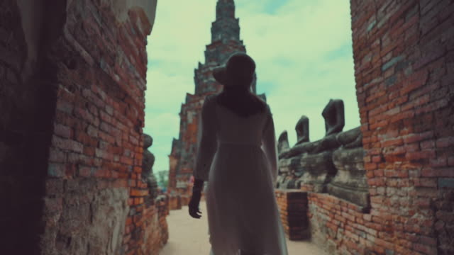 scene slow motion of asian woman enjoy travel old city in chaiwatthanaram temple at ayutthaya, the chaiwatthanaram temple is famous place old city at ayutthaya - wat video stock e b–roll