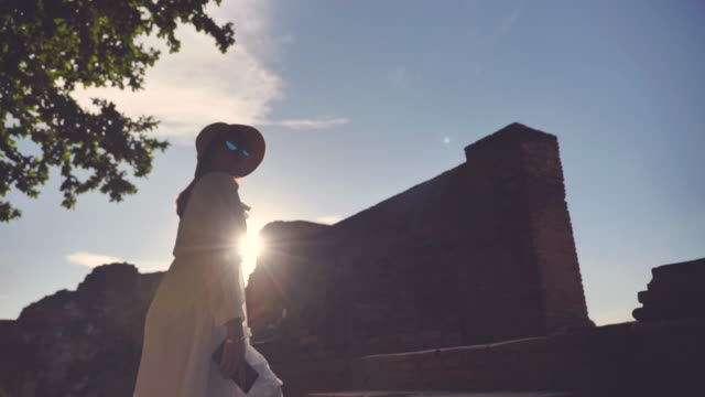Scene slow motion of asian woman enjoy travel old city in Temple at Ayutthaya, Asian woman solo travel at Temple is famous place old city at Ayutthaya