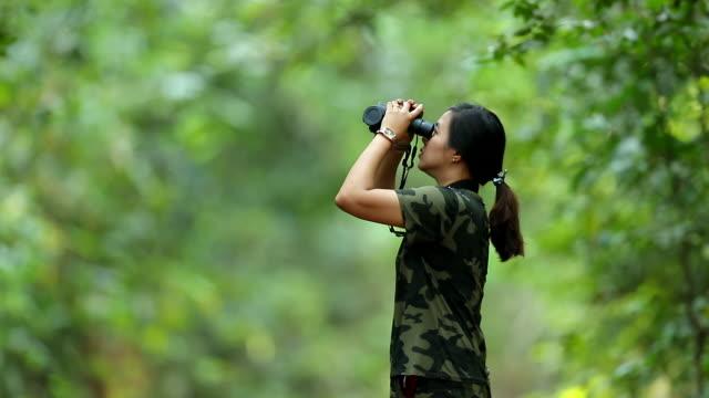 森の中で双眼鏡を使ったアジア人女性のスローモーション、女性旅行、森の中の鳥を探す双眼鏡を使う、人々のアウトドア活動のライフスタイル - バードウォッチング点の映像素材/bロール