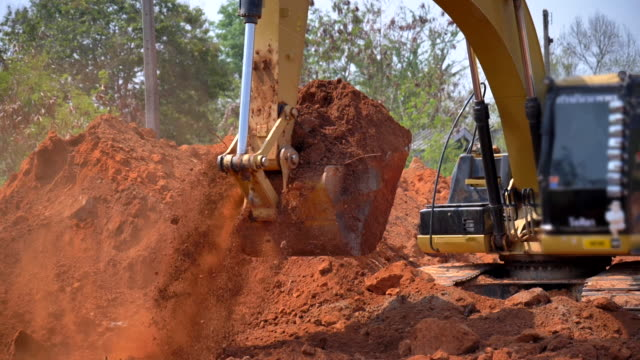 Scene slow motion of excavator bucket digging into the soil at the sunny construction sit