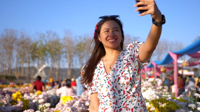 Scene slow motion of joyful asian woman relaxing and using phone selfie a photo flower in field colourful flower