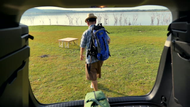 scene slow motion of senior asian male walking and backpack is relaxing and enjoying view near the lake in the summer holidays. he is happy and have fun on holidays, concept road trips in holiday - турист с рюкзаком стоковые видео и кадры b-roll