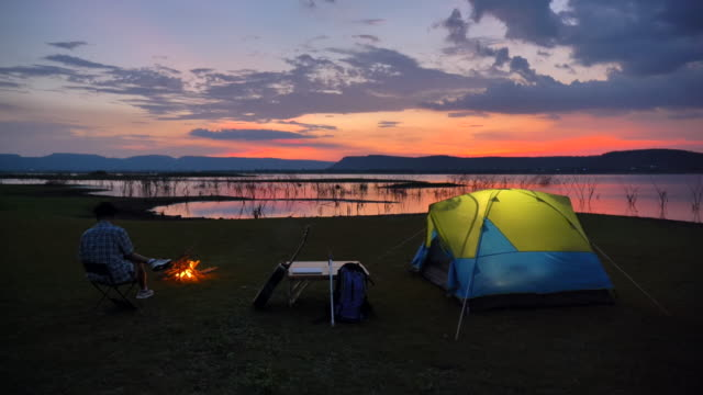 Scene slow motion of senior asian man is sitting near tent and enjoying a campfire view near the lake in the summer holidays.He is happy and have fun on holidays, Relaxation moment. Concept of senior natural everyday life outdoors