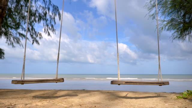 szene zeitlupe der holzschaukel am tropischen strand in thailand, natur hintergrund - schaukel stock-videos und b-roll-filmmaterial