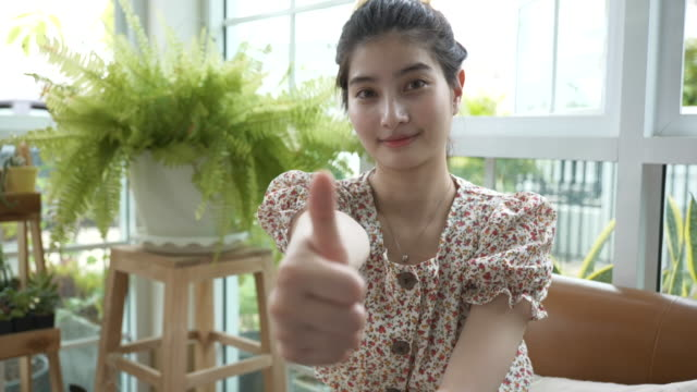 Scene slow motion of young asian woman making ok gesture with her hands with smiling, Relaxation in small garden at greenhouse
