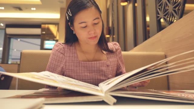 Scene slow motion of young asian woman reading a menu at restaurant, Concept of holiday end of week, Lifestyle of asian woman