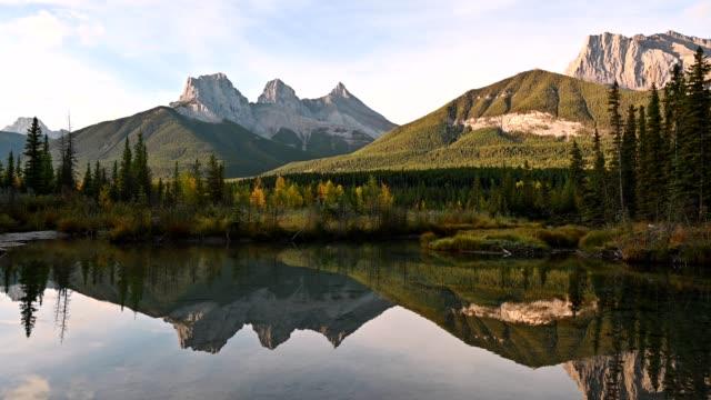 landskap av tre systrar berg reflexion på dammen i höstdal på canmore, banff nationalpark - klippiga bergen bildbanksvideor och videomaterial från bakom kulisserna