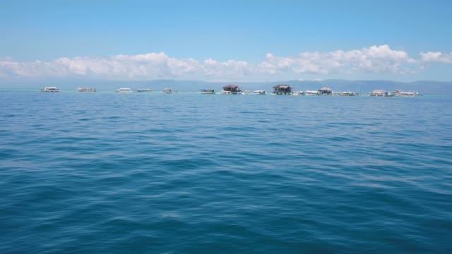 熱帯の島に船や家を持つ島のボートからの風景の海景。 - 叙情的な内容点の映像素材/bロール