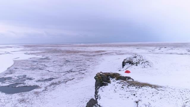 stockvideo's en b-roll-footage met ws scenic aerial view camping tent op klif met uitzicht op afgelegen sneeuw bedekt landschap, ijsland - minder dan 10 seconden