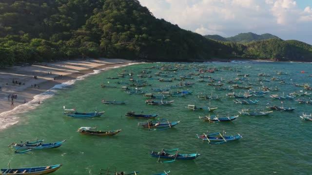 vidéos et rushes de vue aérienne scénique d'un grand nombre de bateaux sur le bord de mer sur nusa penida - indonésie
